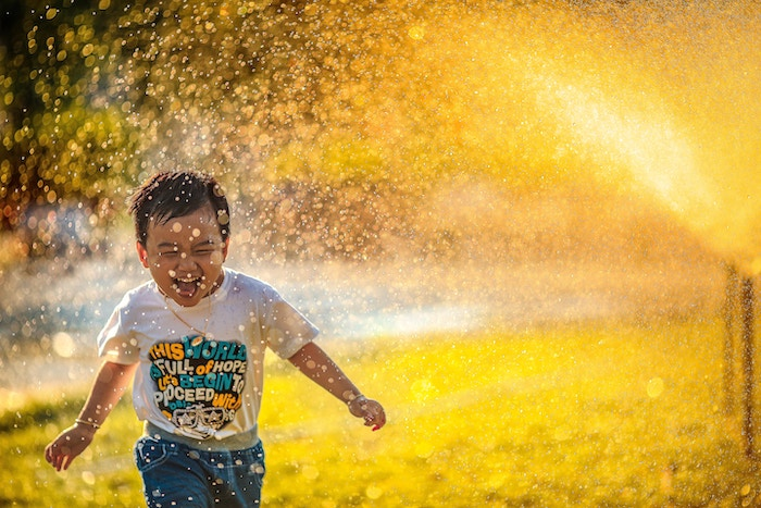 kid running through sprinkler