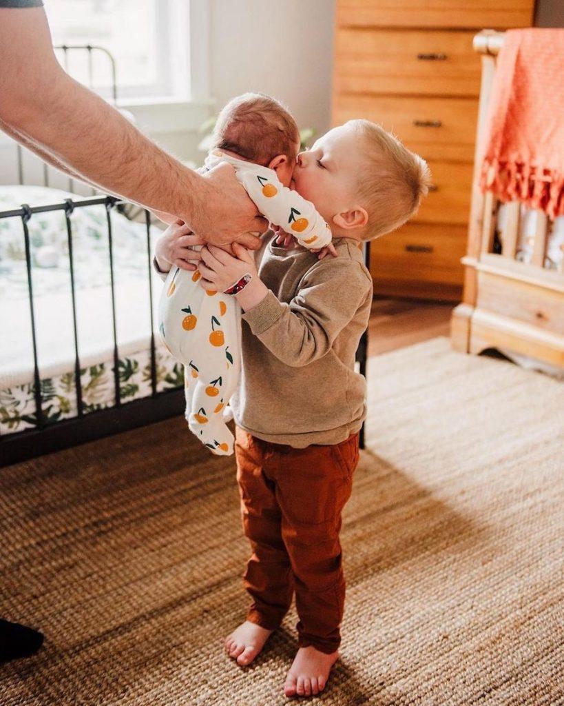little boy kissing baby sibling